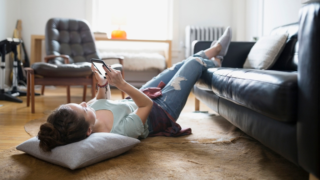 Photo of a woman laying with feet up texting cell phone